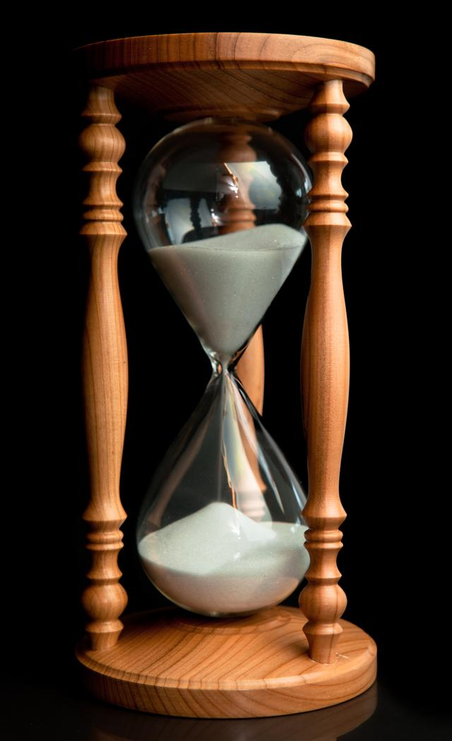"""Sand flowing inside of hourglass"" stock image"