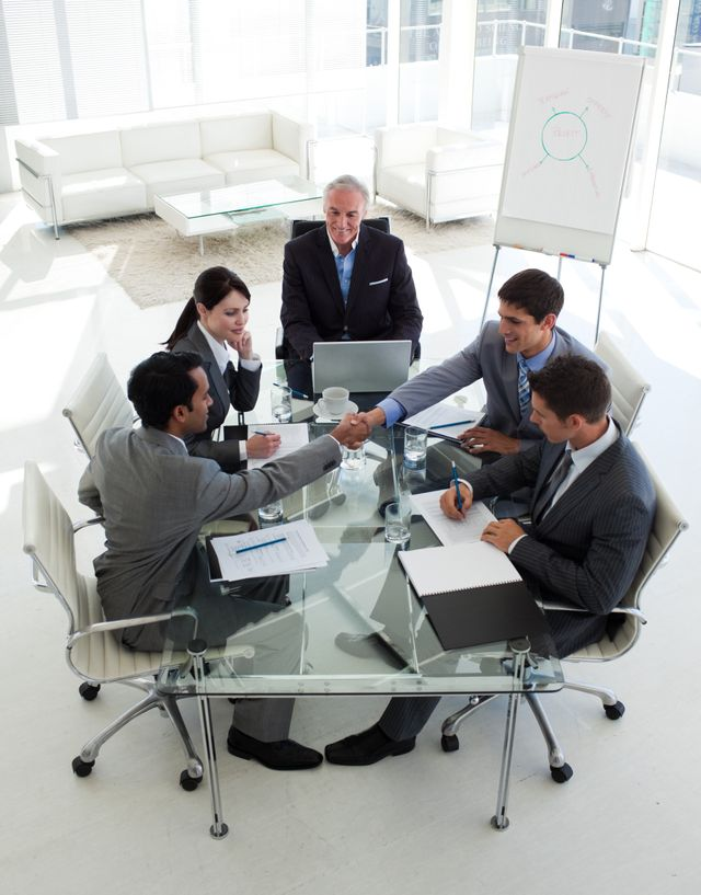 """""""Businessmen closing a deal in a meeting"""" stock image"""