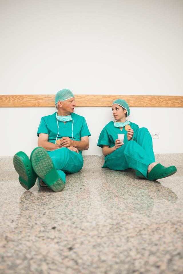 """Surgeons sitting on the floor"" stock image"