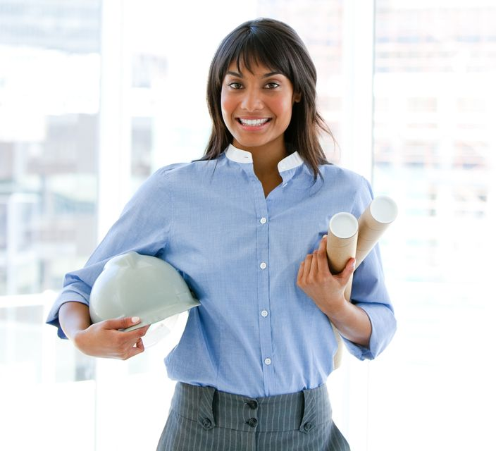 """Smiling female architect holding a hardhat and blueprints standing"" stock image"