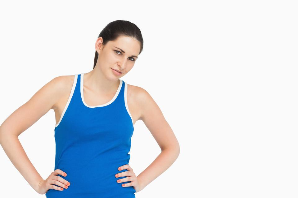"""Serious brunette in sportswear hands on hips"" stock image"