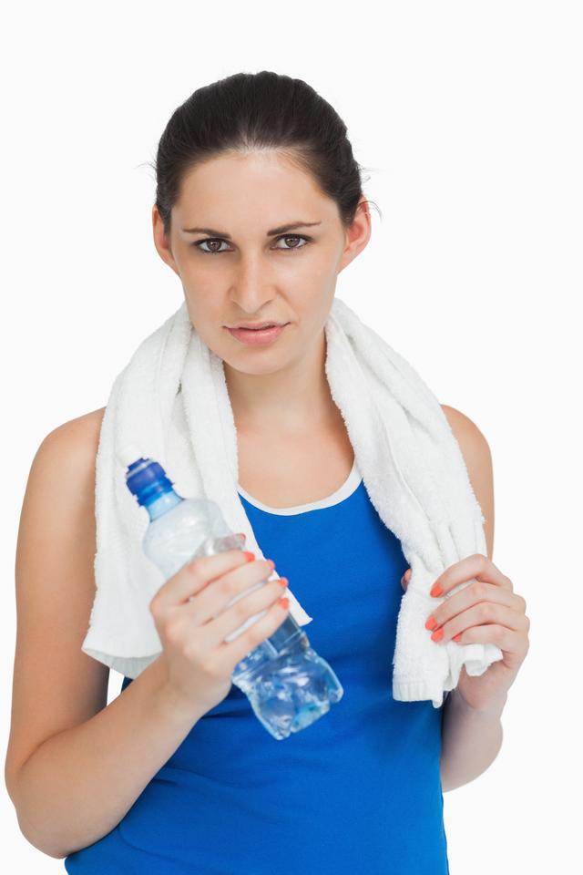 """Brunette woman in sportswear with a towel and a bottle"" stock image"