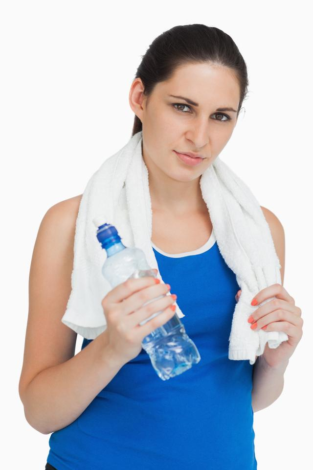 """Brunette wearing sportswear with a towel and a bottle"" stock image"