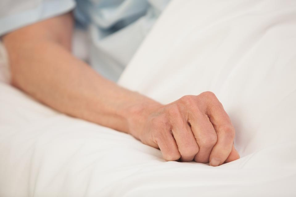 """Elderly arm in hospital bed"" stock image"