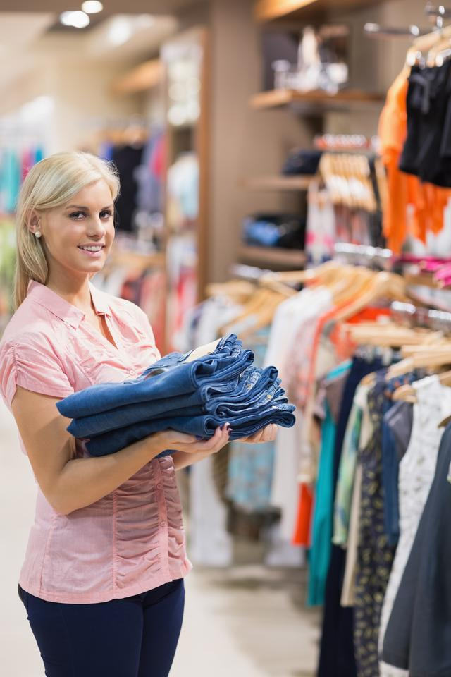 """""""Woman standing holding pants"""" stock image"""
