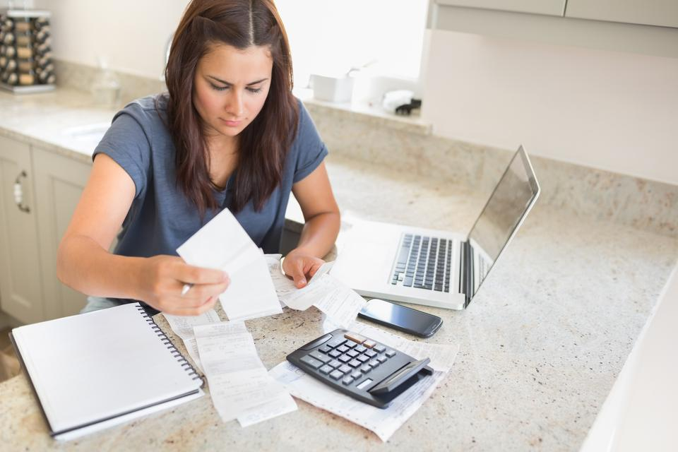 """""""Woman calculating bills with laptop"""" stock image"""