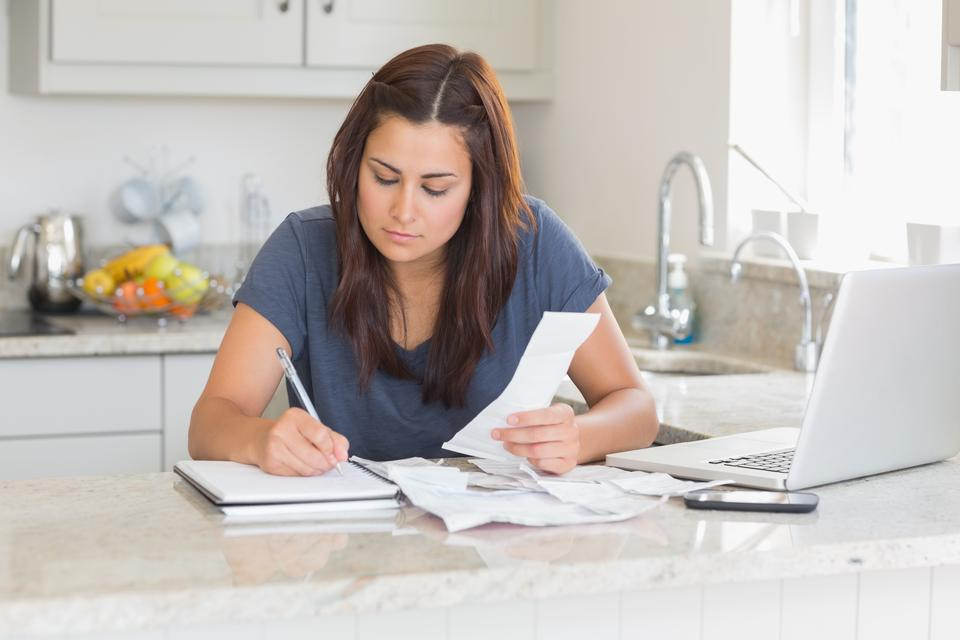 """""""Woman calculating receipts with laptop"""" stock image"""