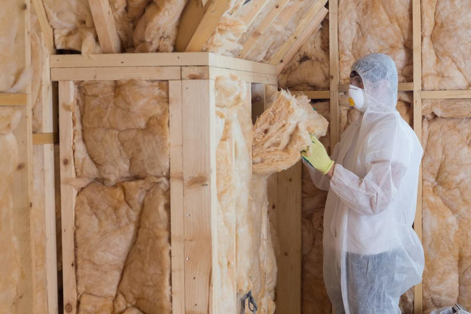 """Worker filling walls with insulation material"" stock image"