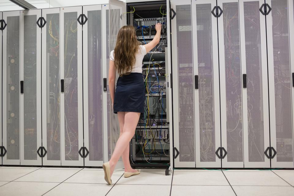 """Woman standing in the hallway and fixing wires in data center"" stock image"