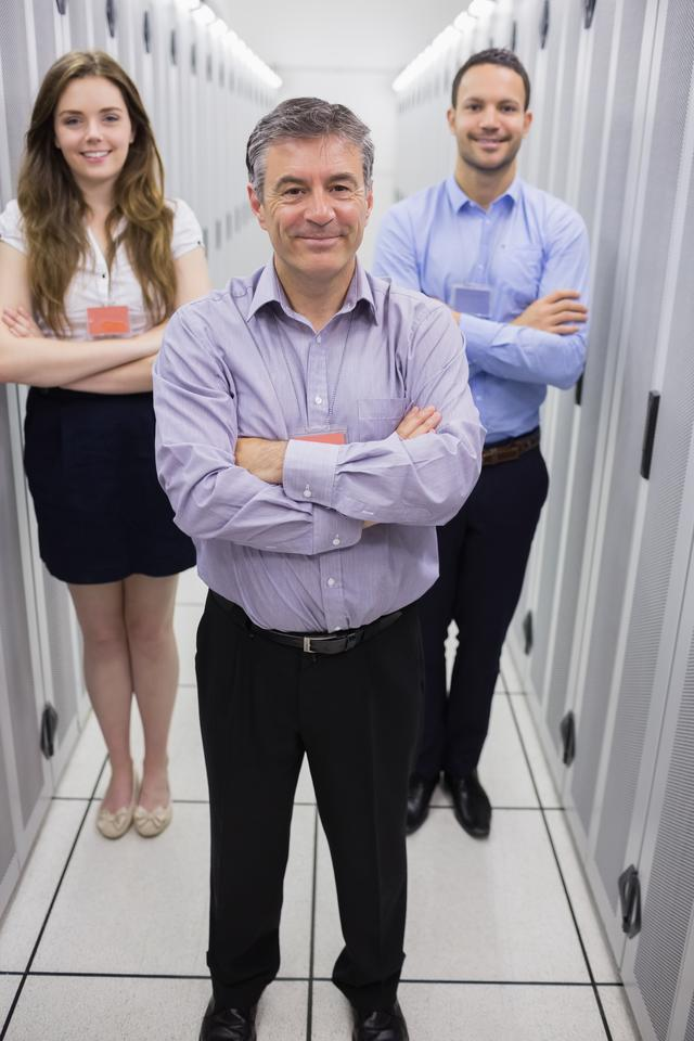 """Smiling technicians standing in data center"" stock image"