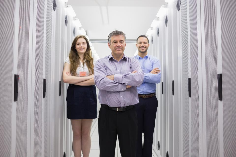 """Three smiling technicians standing in data center"" stock image"
