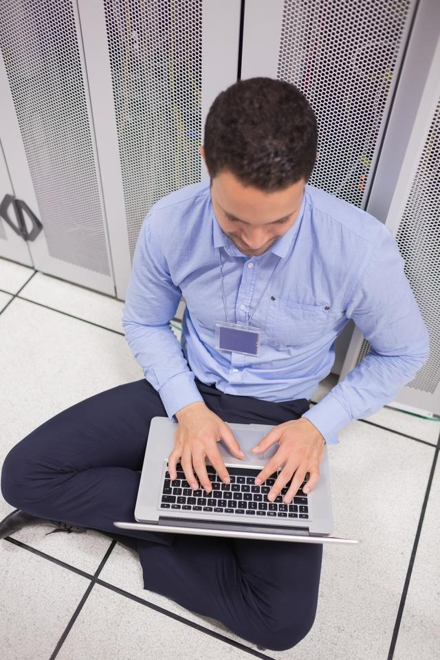 """Man using his laptop in data center"" stock image"