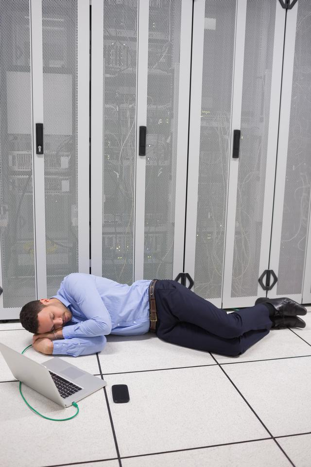 """Man napping in data center"" stock image"