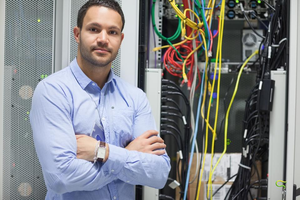 """Man standing with arms crossed in data center"" stock image"