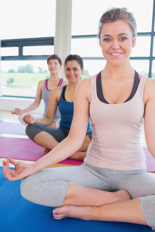 """Happy women sitting in easy yoga pose"" stock image"