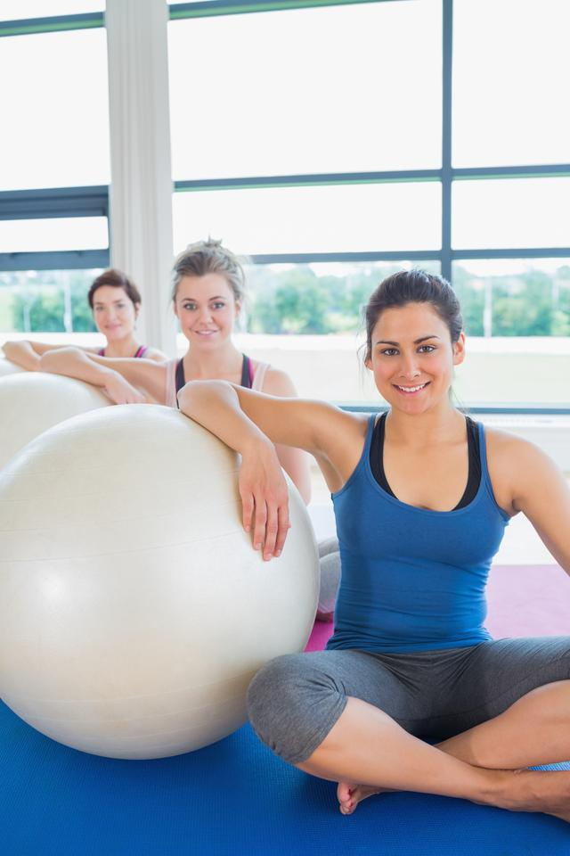 """Women sitting with exercise balls"" stock image"