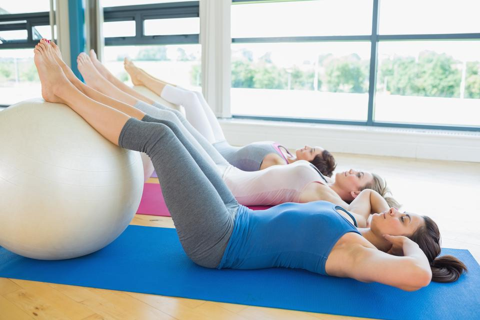 """Women doing sit ups with exercise ball"" stock image"