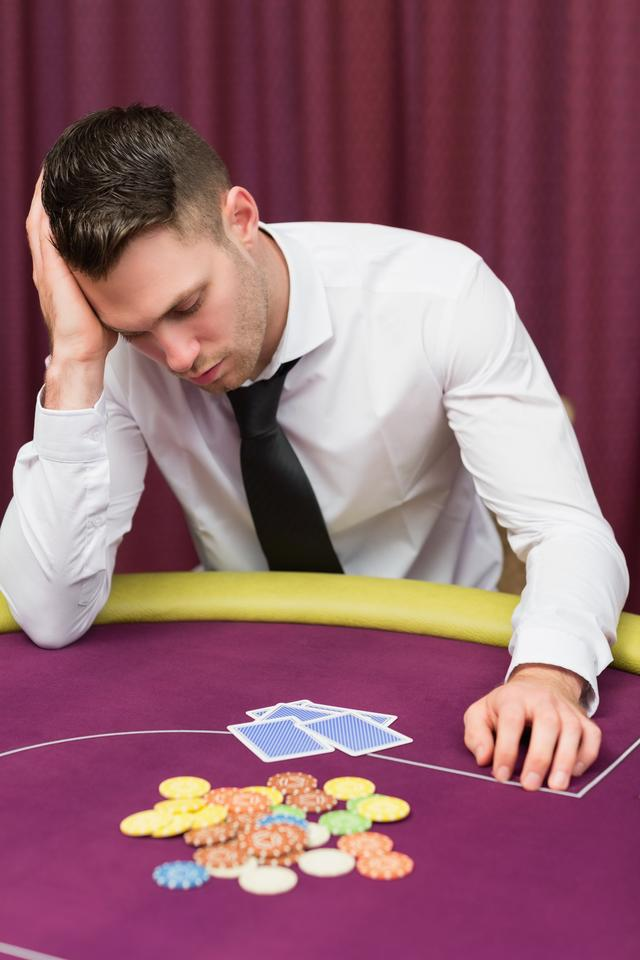 """""""Man leaning on poker table looking disappointed"""" stock image"""