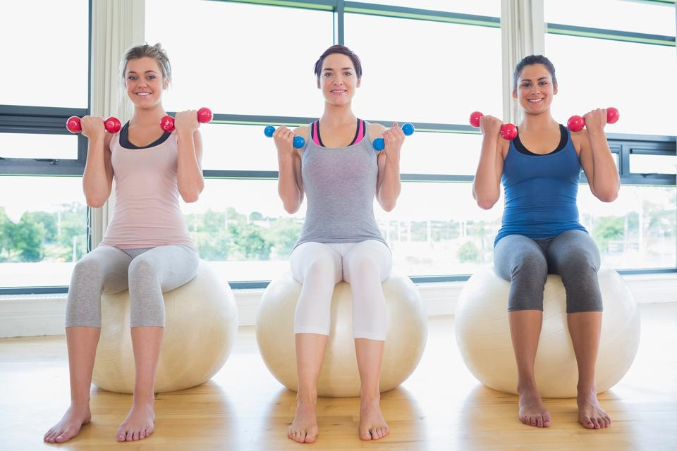 """Women lifting weights on exercise balls"" stock image"