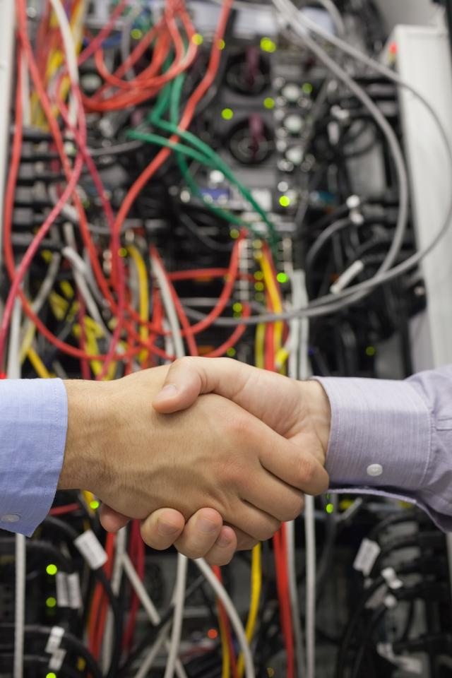 """Handshake in front of a data store"" stock image"
