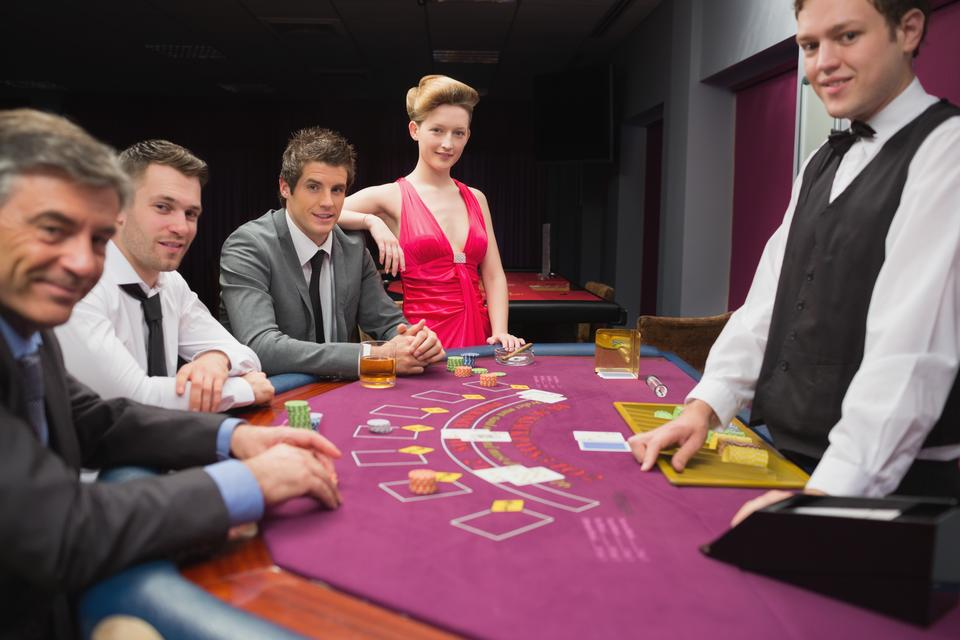 """People sitting at blackjack table and smiling"" stock image"