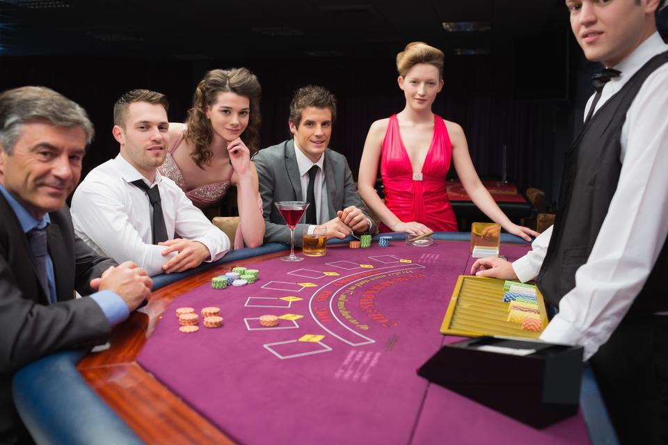 """People sitting at the blackjack table smiling at the casino"" stock image"