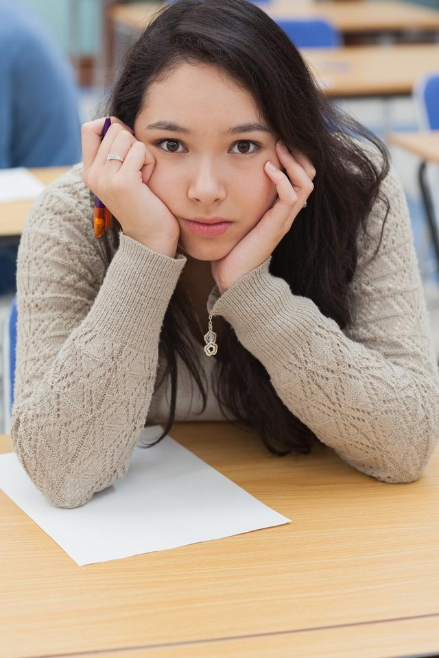 """""""Woman with head in hands in exam hall"""" stock image"""