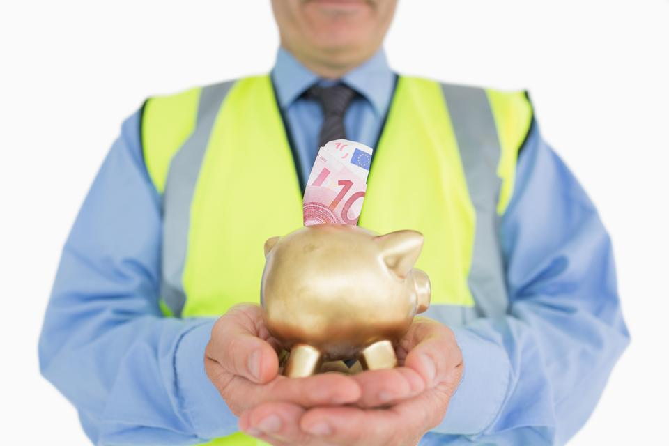 """Man in vest holding a piggybank"" stock image"