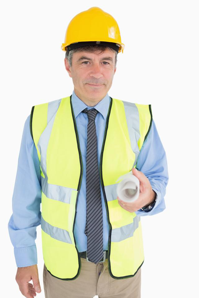 """Man in helmet and vest holding a plan"" stock image"