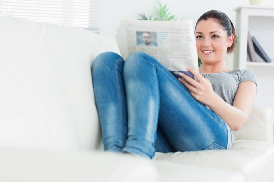 """Relaxing woman lying on the couch and reading newspaper"" stock image"