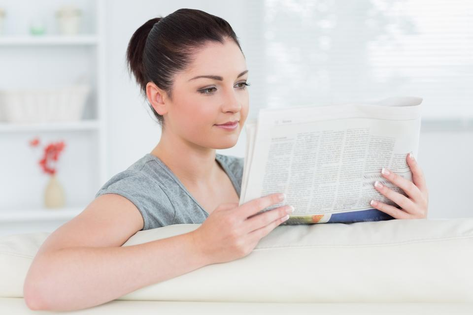 """Woman sitting on the couch and reading newspaper"" stock image"