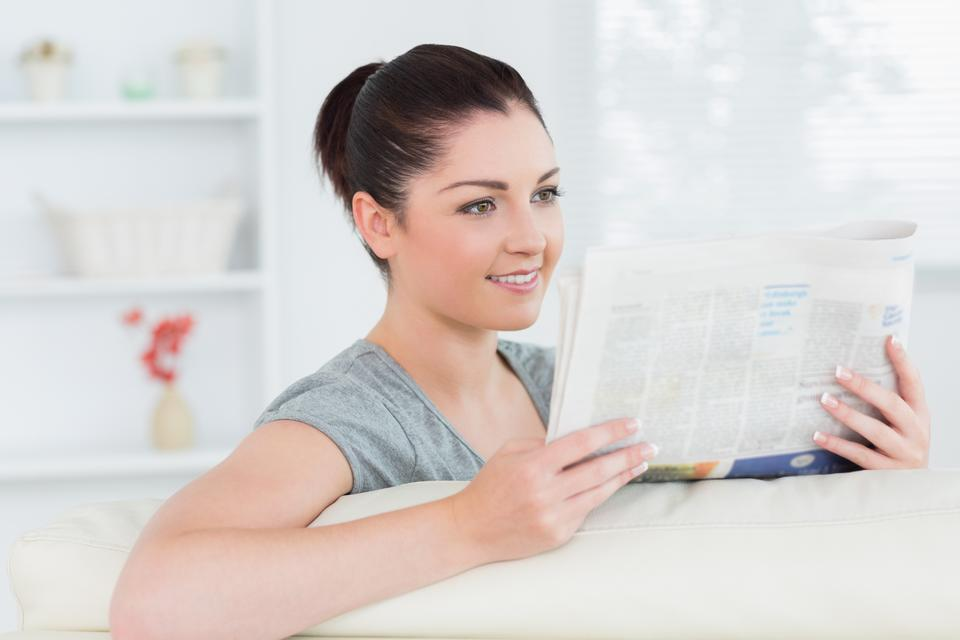 """Smiling woman sitting on the couch and reading newspaper"" stock image"