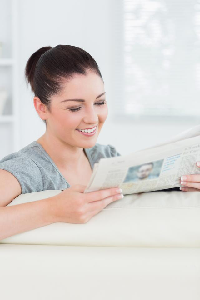 """Smiling woman reading the news while sitting on a couch"" stock image"