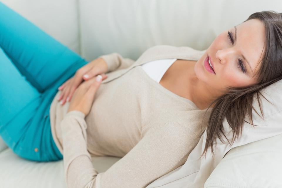 """""""Sick woman lying on sofa with stomach ache"""" stock image"""