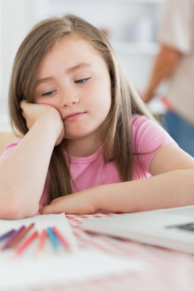 """""""Girl sitting looking bored with paper and colouring pencils"""" stock image"""