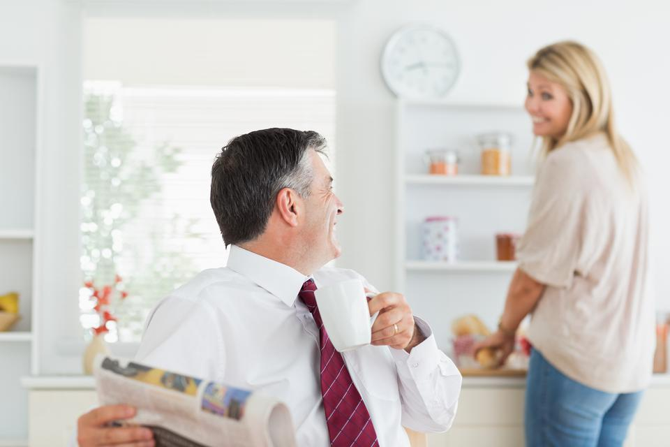 """Couple laughing together in kitchen before work"" stock image"