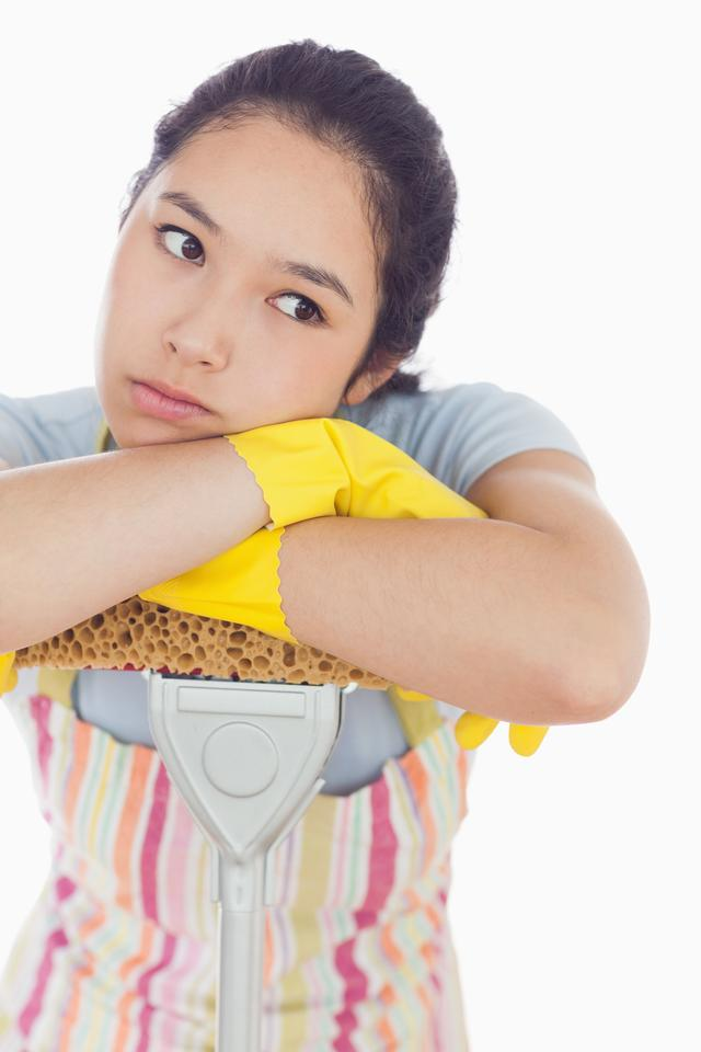 """""""Fed up woman leaning on the mop"""" stock image"""