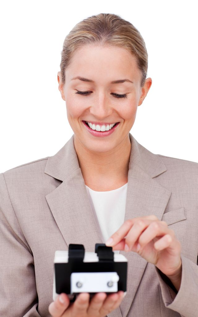 """""""Happy businesswoman consulting a business card holder"""" stock image"""