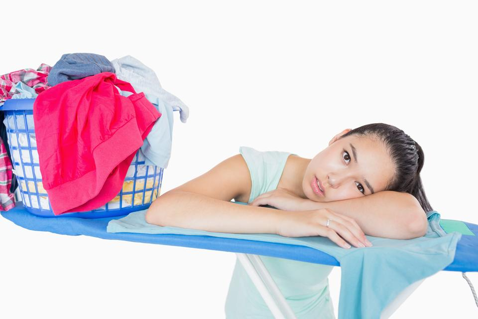 """""""Woman with head resting on an ironing board"""" stock image"""