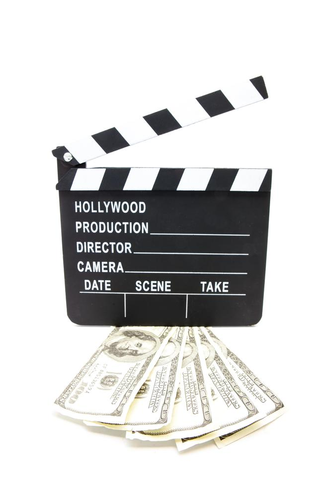 """Fanned out dollars under film slate"" stock image"