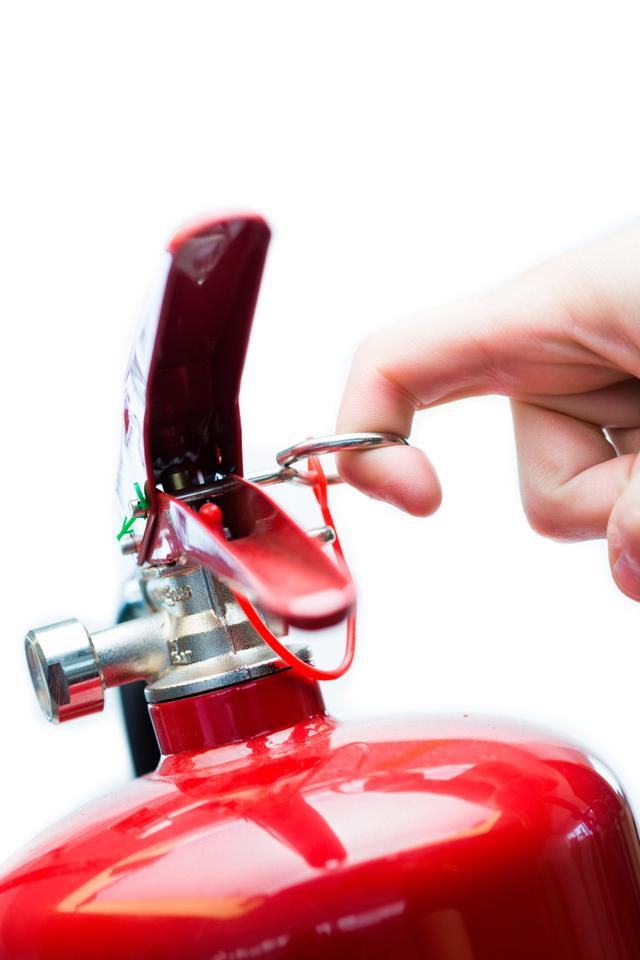 """""""Hand pulling safety pin from fire extinguisher"""" stock image"""