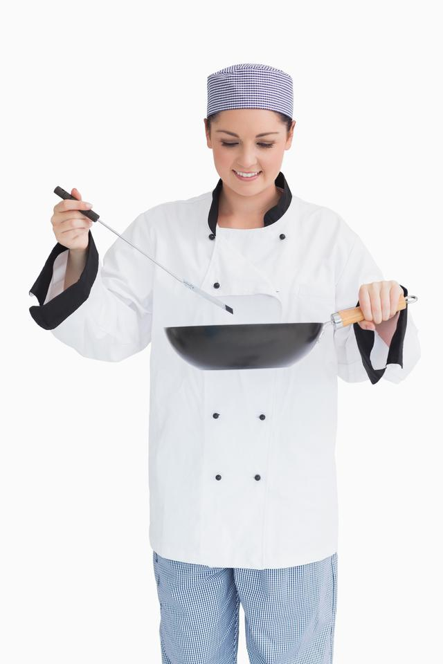 """Smiling cook cooking with wok and spoon"" stock image"