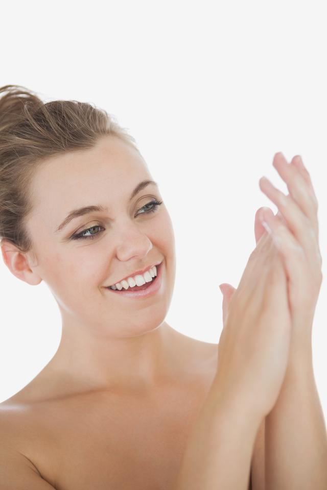 """Woman applying moisturizer on hands"" stock image"