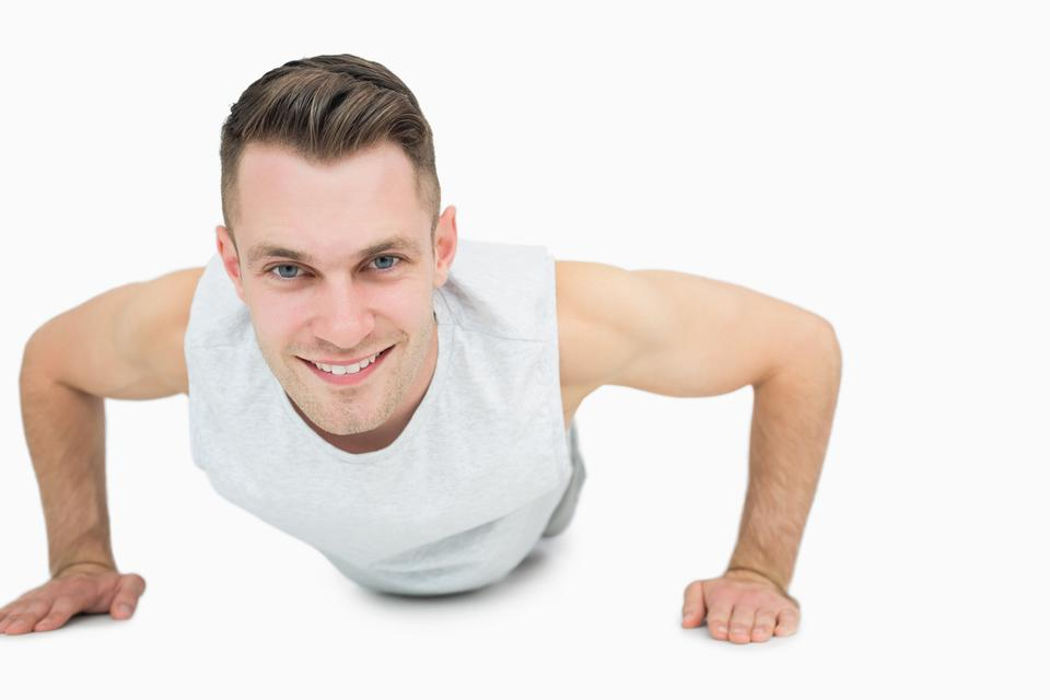 """""""Portrait of smiling young man doing push ups"""" stock image"""