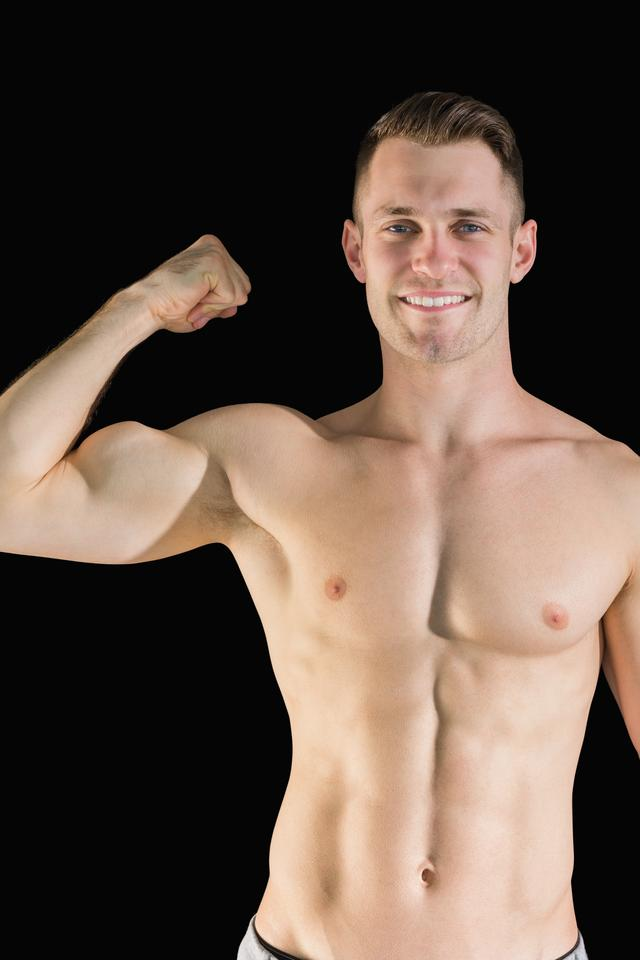 """Portrait of smiling young man flexing muscles"" stock image"