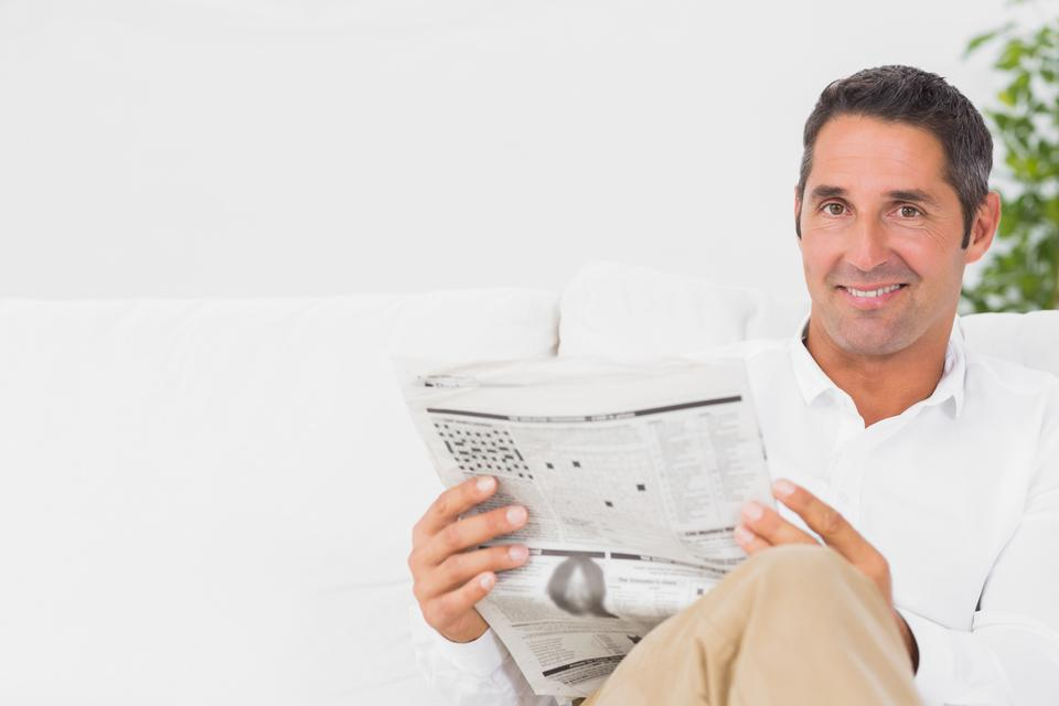 """Smiling man reading a newspaper"" stock image"