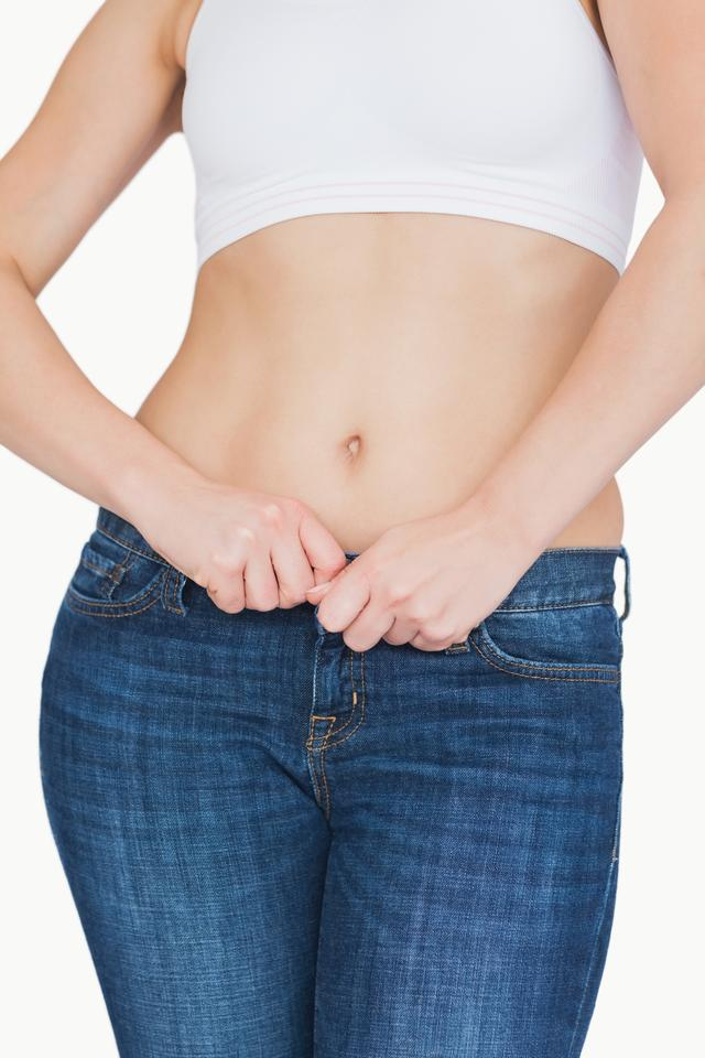 """Midsection of slim woman buttoning jeans"" stock image"