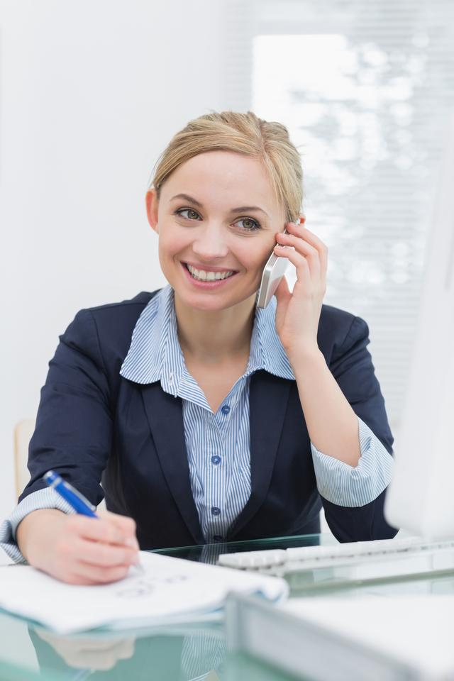 """""""Smiling business woman writing while on call at office"""" stock image"""