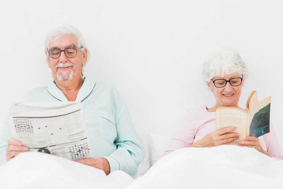 """Happy couple reading in bed"" stock image"