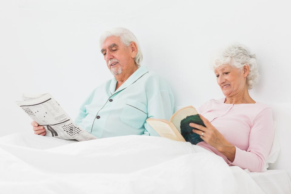 """Smiling couple reading in bed"" stock image"